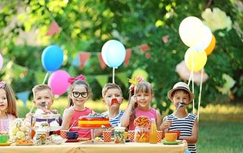 Kids celebrating birthday in park with glasses, mustache and hat props