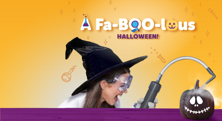 A mad science instructor wearing a witch hat using the mad science smoke shower machine over a black pumpkin.